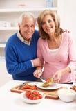 Couples aînés effectuant le sandwich dans la cuisine Photo libre de droits