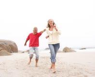 Couples aînés en vacances fonctionnant le long de la plage Images libres de droits