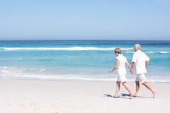 Couples aînés en vacances fonctionnant le long de la plage sablonneuse Images libres de droits
