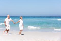 Couples aînés en vacances fonctionnant le long de la plage sablonneuse Image stock