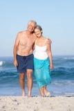 Couples aînés en vacances marchant le long de la plage sablonneuse Photos stock