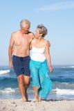 Couples aînés en vacances marchant le long de la plage sablonneuse Photographie stock