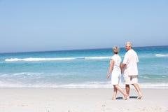 Couples aînés en vacances marchant le long de la plage sablonneuse Image libre de droits