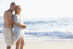 Couples aînés en vacances marchant le long de la plage sablonneuse Photographie stock libre de droits