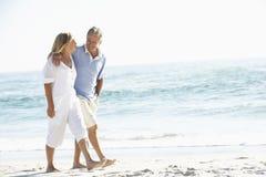 Couples aînés en vacances marchant le long de la plage sablonneuse Images libres de droits
