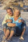 Couples aînés en vacances se reposant sur la plage sablonneuse Images libres de droits