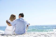 Couples aînés en vacances se reposant sur la plage sablonneuse Photo stock