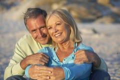 Couples aînés en vacances se reposant sur la plage sablonneuse Photos stock