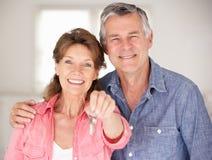 Couples aînés entrant dans la maison neuve photographie stock libre de droits