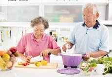 Couples aînés faisant cuire dans la cuisine Photographie stock