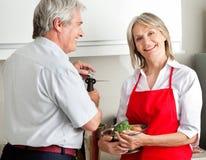 Couples aînés faisant cuire dans la cuisine Image libre de droits