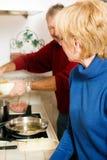 Couples aînés faisant cuire des paraboloïdes dans la cuisine Photographie stock libre de droits