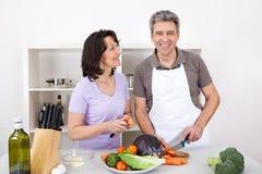 Couples aînés faisant cuire le déjeuner à la maison Image libre de droits