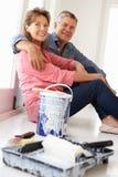 Couples aînés faisant la pause de décorer la maison Image stock