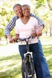 Couples aînés faisant un cycle en stationnement photos libres de droits