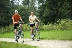 Couples aînés faisants du vélo Photographie stock libre de droits