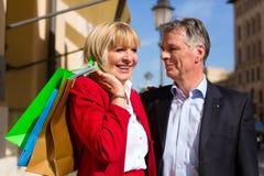 Couples aînés flânant par les achats de ville Images libres de droits