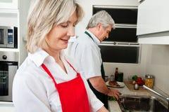 Couples aînés fonctionnant dans la cuisine Photos stock