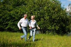 Couples aînés fonctionnant sur un pré Photographie stock libre de droits