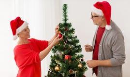 Couples aînés heureux décorant l'arbre de Noël Images stock