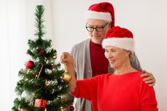 Couples aînés heureux décorant l'arbre de Noël Photos libres de droits