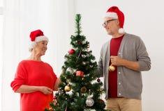 Couples aînés heureux décorant l'arbre de Noël Images libres de droits