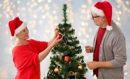 Couples aînés heureux décorant l'arbre de Noël Photographie stock libre de droits