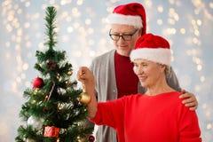 Couples aînés heureux décorant l'arbre de Noël Image stock