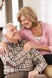 Couples aînés heureux détendant à la maison Image stock
