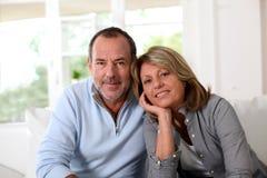 Couples aînés heureux détendant à la maison Photographie stock libre de droits