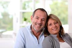 Couples aînés heureux détendant à la maison Photographie stock