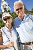 Couples aînés heureux jouant au golf ensemble Images libres de droits