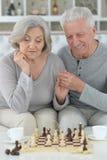 Couples aînés heureux jouant aux échecs Photos stock