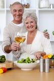 Couples aînés heureux mangeant d'une salade dans la cuisine Photos libres de droits