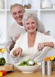 Couples aînés heureux mangeant d'une salade dans la cuisine Photographie stock