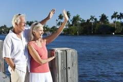 Couples aînés heureux ondulant à l'extérieur par la mer Image libre de droits