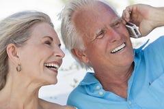 Couples aînés heureux parlant sur le téléphone portable mobile Images stock