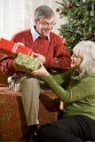 Couples aînés heureux permutant des cadeaux de Noël Photos stock