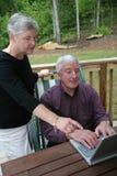 Couples aînés heureux sur l'ordinateur Photos libres de droits