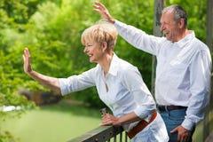 Couples aînés heureux sur les mains de ondulation de passerelle image stock