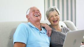 Couples aînés heureux utilisant un ordinateur