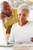 Couples aînés inquiétés utilisant l'ordinateur portatif à la maison Photos stock