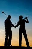 Couples aînés jouant au golf au coucher du soleil Image stock