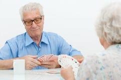 Couples aînés jouant avec des cartes Images stock