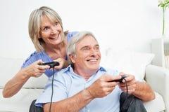 Couples aînés jouant des jeux vidéo Photo stock