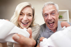 Couples aînés jouant le jeu visuel de console Images stock