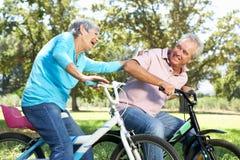 Couples aînés jouant sur les vélos des enfants Image libre de droits