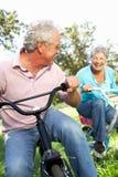 Couples aînés jouant sur les vélos des enfants Photos libres de droits