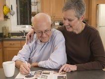Couples aînés lisant attentivement le catalogue Image libre de droits