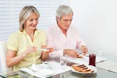 Couples aînés mangeant le déjeuner Photos libres de droits